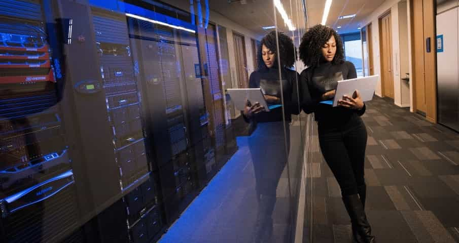 A woman stands in a Microsoft Azure data center while looking at a laptop